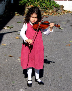 Picture of little girl in a pink dress playing a fiddle
