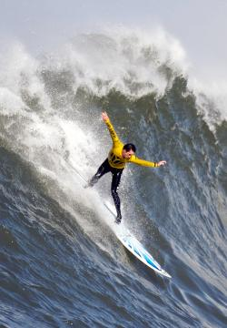 A man in a yellow top and tight black trousers on a surfboard with his arms outstretched on a large wave