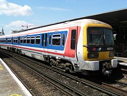 The front of a Networker train in red, white and blue Network SouthEast livery from the early 1990s, at a station.