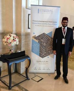 "A young man of South Asian appearance with a shortish beard, wearing a dark suit over a white shirt and red striped tie, standing next to a tall sign which reads ""4th Forum for Promoting Peace in Muslim Societies: Global Peace and the Fear of Islam -- Roadblocks on the road to Radicalism"". Next to that is an ornate wooden table with a jar with a large display of flowers in it."