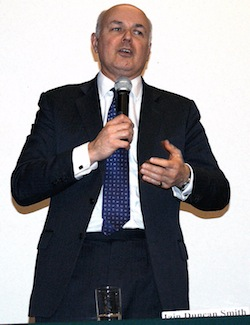 Picture of Iain Duncan Smith, a white man with a grey suit and a blue patterned tie, holding a microphone. He has a glass of water and a name sign in front of him.