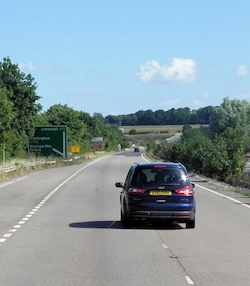 "A two-lane carriageway of a main road (the other two-lane carriageway is mostly hidden behind plants in this photograph). There is a sign pointing straight ahead for ""Lowestoft A12"" and off to the left for ""Framlingham B1116, Wickham Mkt and Orford B1078"". A metallic dark blue Ford car is in the left-hand lane although it is partly in the right-hand lane, indicating that it is pulling in or pulling out. A yellow sign points off the road for ""diverted traffic"". There is a deep blue sky with a few small white clouds. There are trees along the left side of the road and fields and hedgerows in the background."