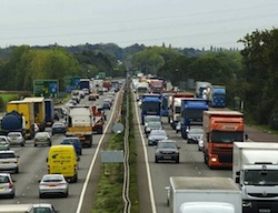 Picture of a dual carriageway full of cars and trucks, and a green direction sign on the left