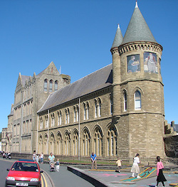 A Victorian stone building with two storeys, with a small round and larger octagonal tower in the foreground. Both towers have pointed spires and the larger tower have paintings of people set into them.
