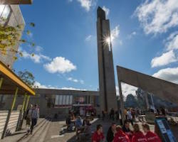 A concrete student union building with a glass frontage, next to a concrete brutalist bell tower and a temporary theatre stand, with people sitting around tables. The sky is deep blue with a few fluffy clouds