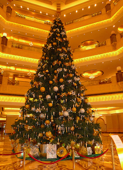 A picture of a Christmas tree decorated in large baubles and other decorations in the ornate lobby of a hotel; four storeys can be seen behind it.