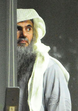 Picture of Abu Qatada, a white man with a dark complexion with a long grey beard, wearing a loose beige Arab head covering and a light grey top