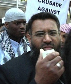 Picture of Michael Adebolajo, a Black African man wearing a white cap and robe with a black and white checked Palestinian-style scarf round his neck, in front of Anjum Choudhary, a South Asian man with a beard wearing a black jacket, who is speaking into a microphone