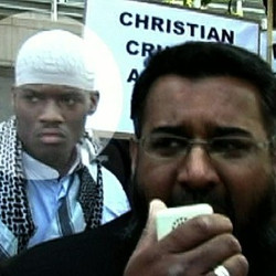 Picture of Michael Adebolajo, a young black man with a plain white cap, standing next to Anjum Choudary, a South Asian bearded man who is holding a megaphone, with part of a banner behind them