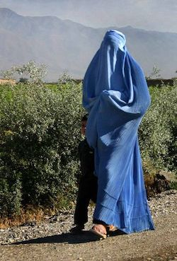 A woman walking along a mud road wearing a blue full-length burqa which covers the whole of her body from head to foot. There are bushes behind her and mountains in the background.
