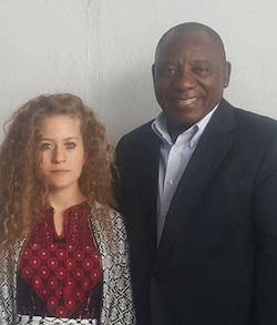 Picture of Ahed Tamimi, a white teenage girl with wavy light brown hair wearing a red and black patterned top under a black and white patterned jacket with a black and white Palestinian keffiyeh tied at her waist, standing next to Cyril Ramaphosa, a large Black man in late middle age wearing a shirt without a tie under a black blazer.