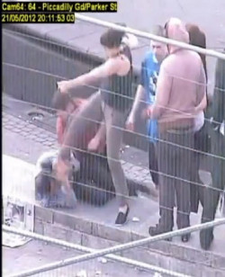 Picture of Amanda Lowe, a white woman wearing a black sleeveless top and grey trousers, kicking a man in the head, with three other people behind her.