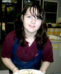 Picture of Amy el-Keria, a young white girl with dark hair brushed across her forehead, wearing a maroon T-shirt with a dark blue apron over it, holding a plate of unidentifable food in both hands.