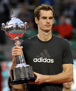 Picture of Andy Murray, a white man wearing a black Adidas T-shirt, holding a silver trophy.