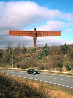 A picture of the Angel of the North, a metal sculpture of an 'angel' with long outstretched wings, on a hill with a road passing beneath it.