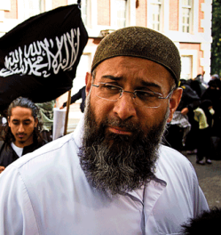 Picture of Anjem Choudary, a man of south Asian apperance wearing a white robe with a black and white Shahada flag behind him.