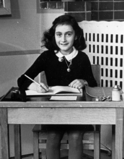 A picture of a young Anne Frank sitting at an old-fashioned desk with an inkwell