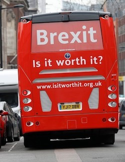 "The back of a red coach with the slogan ""Brexit: Is It Worth It?"" and the URL www.isitworthit.org.uk below, making its way down a narrow London street with cars either side"
