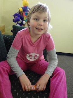 Picture of Ayn van Dyk, a 9-year-old (at the time of this photo) white girl with short blonde hair, wearing a pink top and trousers, the top with grey sleeves and a white CND-type logo on it. She is sitting on a green sofa with a set of brightly-coloured soft toys behind it.