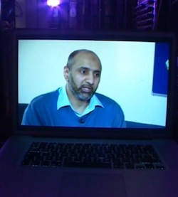 Picture of Babar Ahmad on a laptop screen, being interviewed for Newsnight from prison