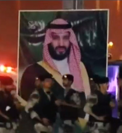 A still showing a group of soldiers marching in front of a larger-than-life portrait of crown prince Muhammad bin Salman, a middle-aged dark-white man with a thick black moustache and beard, wearing a red-and-white keffiyeh or Arab-style headscarf.