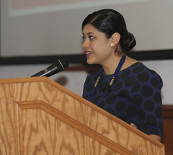 Picture of Beenish Ahmed, a young Asian woman wearing a dark blue and black top (or dress), standing at a lectern with a microphone