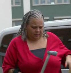 A light brown-skinned woman with braided hair, wearing a red jumper and a black top under it, holding a crutch in her hand, getting out of a metallic grey Nissan car