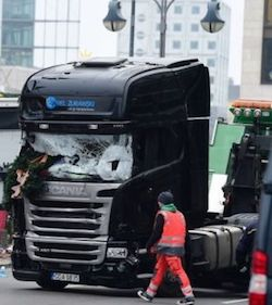A black Scania R-type tractor unit with the owner's name 'Ariel Suraski' on its headboard, and a broken window