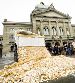 A 32-tonne tipper truck dumps a load of coins in front of a town hall, as people stand and applaud.