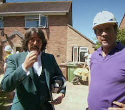 Laurence Llewelyn-Bowen, a 50-year-old white man with a beard and moustache and shoulder-length hair, wearing an open-necked white shirt with a green suit jacket over it, holding a hat decorated with white skulls under his left arm, standing next to Nick Knowles, a middle-aged, clean-shaven white man wearing a purple polo-neck T-shirt with a white hard hat on his head; a red-brick house can be seen in the background with workmen with flourescent jackets and hard hats can be seen behind the the two men.