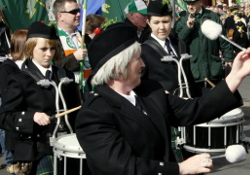 Image of a St Patrick's Day parade in Birmingham, showing at its centre a white woman and two girls playing drums, with various other white people wearing Irish flags and similar regalia