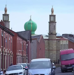 A view down a narrow street which is lined with old, small, red-brick terraced houses. Cars are parked next to them and a red Mercedes van can be seen on the other side. At the end of the street is a yellow-brick mosque with a green 'pepperpot' dome and a small minaret.