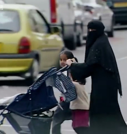 A woman wearing black robes with a matching niqaab (face-covering) crossing the road, pushing a buggy with two young girls, both of South Asian appearance, walking beside her.
