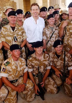 Picture of Tony Blair surrounded by a group of soldiers in army fatigues, some standing and some kneeling.