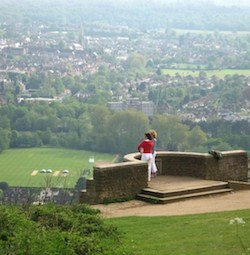 A picture of the view from Box Hill. In the foreground is a viewing platform with a semicircular wall with two steps up; two white women, one wearing a red jumper and white pair of trousers and holding something under her arm, the other wearing a blue or grey top and white trousers. Behind the viewing platform there is a steep downward drop, with a playing field, houses and an office building at the bottom of the hill. It is a misty day and the buildings further away appear whitened, while the greenery in the foreground and the viewpoint are clearly visible.