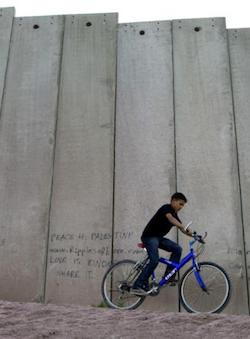 "A boy riding a suspension mountain bike with a bright blue frame in front of the Israeli concrete wall which is about three times his height. A graffito ""Peace 4 Palestine"" appears to his left."