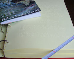 Image of a thin print volume on top of a large ring binder containing the same book in Braille, with a tape measure diagonally across the bottom-right corner.