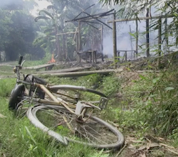 A bicycle abandoned in the grass in front of a burning building in a Burmese Muslim village