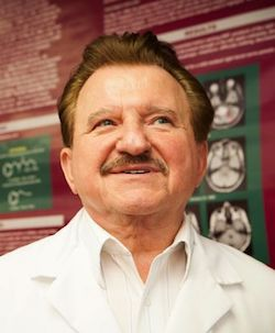 Picture of Stanislaw Burzynski, an elderly white man with brown hair and a short moustache but no beard, wearing an open-necked cream/white striped shirt and a white lab coat over the top, standing in front of a red and green wall display with some images of brain scans on it.