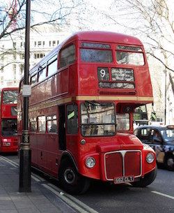 Picture of an old-style red London bus, with the number 9 on the front, under some leafless winter trees in a London street