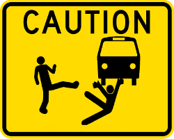 A yellow road sign showing a bus, a person with his foot out, and a person falling under the bus