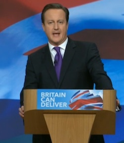 Picture of David Cameron delivering a speech at the 2012 Conservative party conference. He is standing against a British flag background and his lectern has a similar logo, with the slogan 'Britain can deliver'