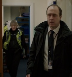 Picture of Sgt Cawood, a middle-aged white woman with blonde hair wearing a police uniform with a yellow flourescent jacket, approaching John Wadsworth, an older, balding white man wearing a dark-coloured suit, from behind in the corridor of a police station