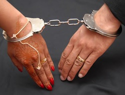 Image of a man's and woman's hands chained together, the woman's decorated with henna