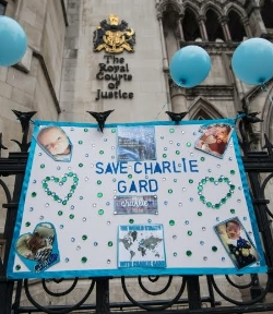 "A handmade poster hung on the railings of the Royal Courts of Justice in London. It is decorated with lots of green and clear glass 'jewels', some arranged in two heart shapes. There are pictures of Charlie, the words ""Save Charlie Gard"" and a map of the world with the words ""The world stands with Charlie Gard"" above and below."