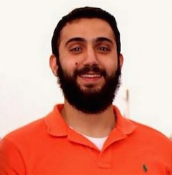 Picture of a young man of Arab appearance, with dark hair and a large dark beard and moustache, with an orange shirt.