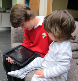 A young white boy wearing a bright red school jumper with a school emblem consisting of a cross inside a diamond with the letters S, A, S and M around the cross. He is holding an iPad and a young child wearing a light grey and white baby suit is sitting looking at it.