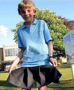 Picture of Chris Whitehead, a boy wearing a skirt, next to his school sign