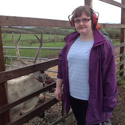 Picture of Claire Dyer wearing red sound-blocking headphones and a purple jacket, next to a fence at a zoo, with a goat behind it