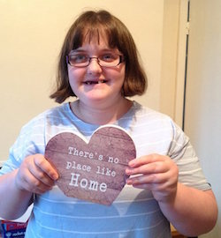 "Claire Dyer, a young white woman with glasses and multiple missing teeth wearing a blue and white striped T-shirt, holding a heart-shaped card with the slogan ""There's no place like home""."